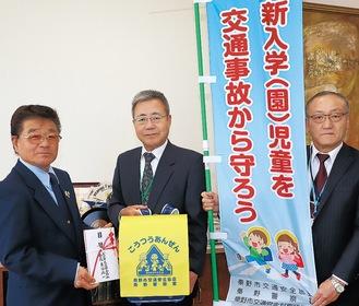 古谷会長(左)は内田教育長(中央)に目録などを手渡した