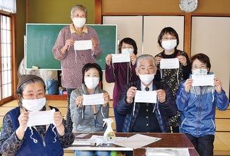 マスクを手にする高橋会長(前列右から2人目)と地域福祉員メンバー