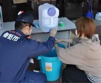 持参したペットボトルに除菌水を入れる市民
