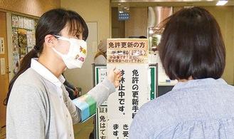啓発マスクを着けて案内する署員(左)