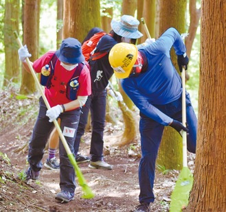 登山道の落ち葉や小枝を取り除く参加者