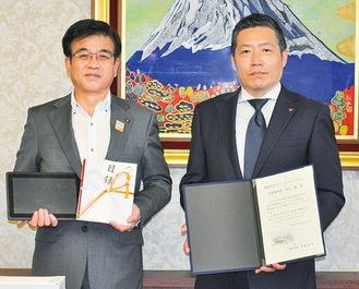 高橋市長に寄付した安川さん(右)