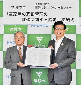 協定書を交わす高橋市長(右)と宮嵜理事長(左)