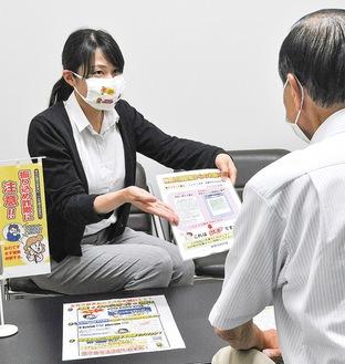 市民から振り込め詐欺の相談を受ける署員。注意を促す啓発マスクをつけ、対応している