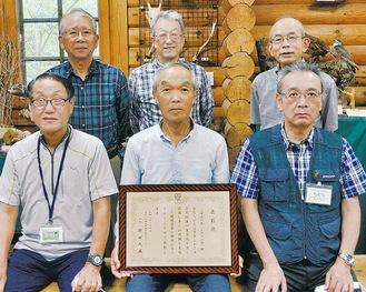 賞状を手にする岡村会長(手前中央)と会員