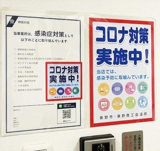 事務所玄関に貼られたステッカーとポスター