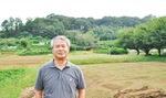 落ち葉をかき集めた山を背景に語る横溝さん