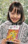 出版された本を手に笑顔の伊藤さん