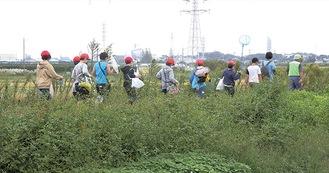 学校から川へ向かう児童ら
