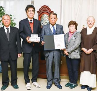 神崎会長(中央)から小山田校長(左から2番目)に翻訳機が手渡された