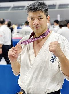 メダルを手に笑顔の梅下さん(提供写真)