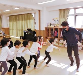 子どもたちと鬼ごっこをする飯田さん(右)