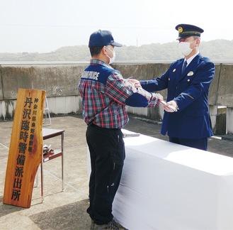 竹田署長からピッケルを受け取る望月隊長(左)