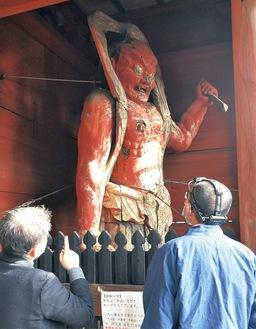 二王像を保護する金網を外し、学芸員(左)と仏像修復士が現地調査を実施