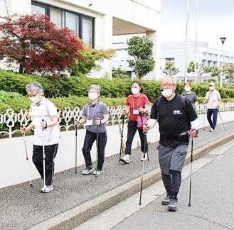 村上さん(右)から指導を受けて歩く参加者