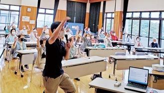 臨床心理士の上野さんによるトレーニング運動に挑戦する参加者ら