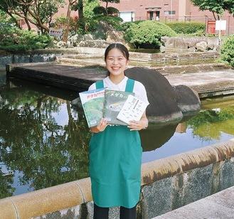 メダカの本を持つ担当者の古田さん。後ろの防火水槽にメダカが繁殖している