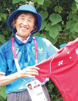 シンガポールの選手から贈られたユニフォームを手にする村田さん