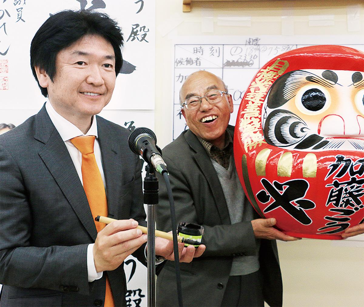 当選を果たし、ダルマに目を入れる加藤氏(左)